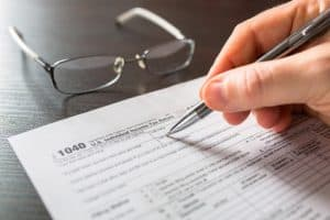 Form 1040 with pen and glasses