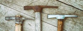 Three old pickaxes on wooden background
