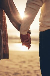 Holding hands on the beach at sunset
