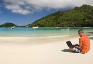 man at beach working on laptop