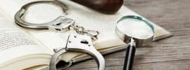 Handcuffs, pipe, and magnifying glass over open book